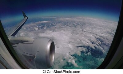 View from a plane window during a flight over puffy clouds.