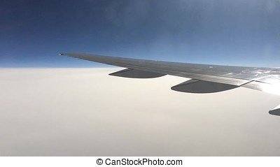 View from a plane window on the wing and the landscape below it. Wing of an airplane flying above the clouds