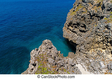 View from a rocky cliff into a turquoise tropical sea.