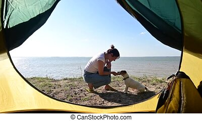 View from a tourist tent on a woman playing with a dog on the seashore