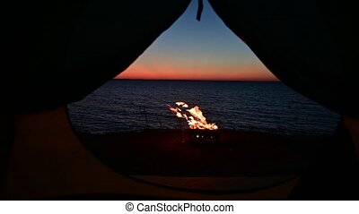 View from a tourist tent on bonfire on the seashore at sunset