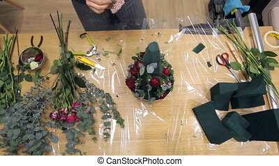 View from above florist working with floral composition on table