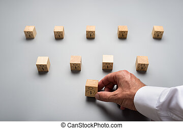 View from above of a businessman arranging wooden cubes with people icon