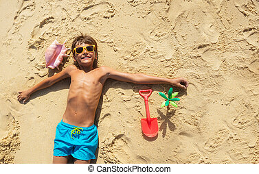 View from above of a happy boy with toys on beach