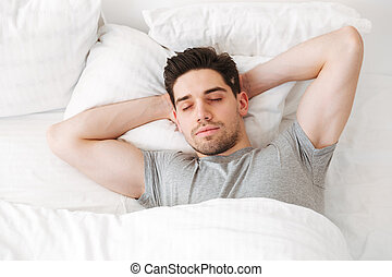 View from above of brunette muscular man in casual t-shirt, sleeping alone at home in bed with white clean linen putting hands under head