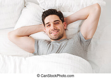 View from above of brunette sexual man in casual t-shirt smiling on camera while lying alone at home in white bed, with putting hands under head