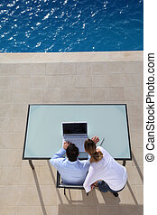 View from above of couple using computer by swimming-pool