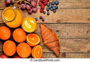 View from above of croissant, orange juice, blueberries, raspberries, apples, oranges - sweet breakfast on wooden table