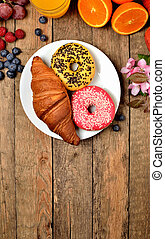 View from above of donuts, croissant, orange juice, blueberries, raspberries, apples - sweet breakfast on wooden table