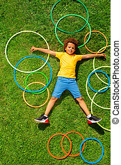 View from above of happy boy on grass with rings