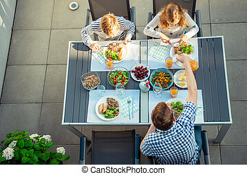 View from above of happy family eating healthy dinner on terrace