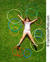 View from above of happy girl on grass with rings