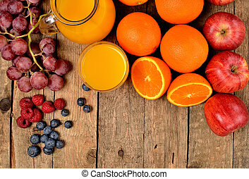 View from above of jug with orange juice, fresh oranges, apples, grapes, raspberries and blueberries on a wooden table - fruit background