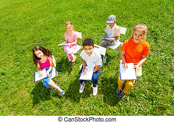 View from above of kids drawing on clipboards