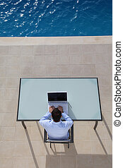 View from above of man using computer by swimming-pool