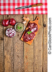 View from above of raw chicken liver on a wooden cutting board, fresh garlic, dried marjoram, oregano, onion, knife and red checkered tablecloth top frame - vertical photo