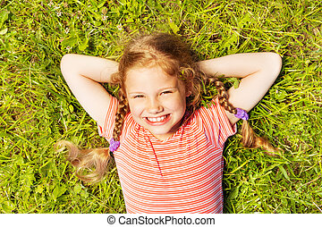 View from above of smiling girl laying on grass