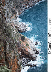 View from above of steep slopes with pine trees and rocky Mediterranean sea shore