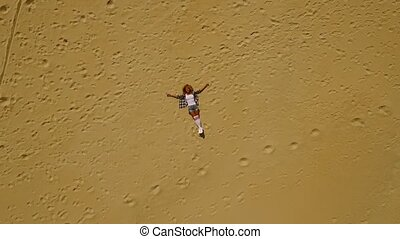 View from above of woman laying in sand - Airborne drone...
