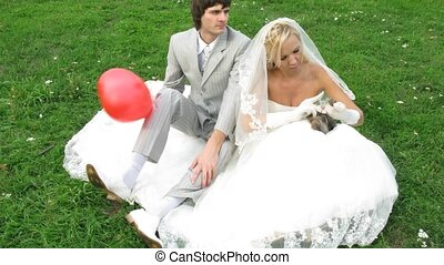 View from above on newlywed pair who poses for photographer on grass, time lapse