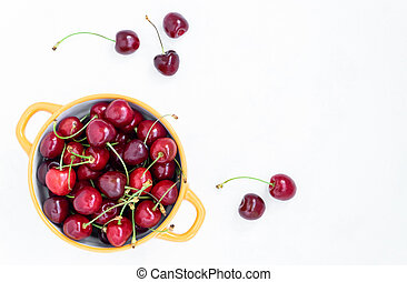 View from above on the bowl with fresh ripe red cherries on a white background