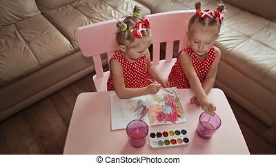 View from above. Two charming little sisters twins draw watercolor on paper, sitting at a table in their room at home.