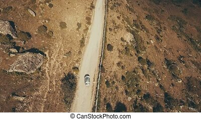 View from above white car moving on winding road mountain