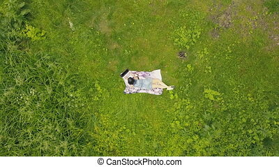 View from above young woman lying on grass and using notebook