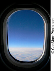 View from aeroplane window onto cloud & blue sky.