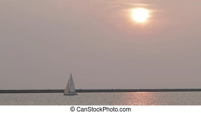 view from afar, a yacht in the haze against the setting sun.