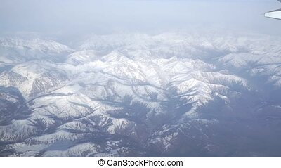 View from airliner porthole with snowy mountains clip