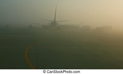 view from airplane window on big aircraft stands in fog on runway on sunrise