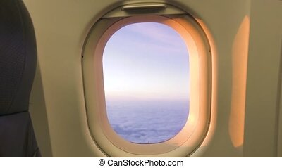 View from airplane window on cloudy sky while sunset. Beautiful landscape sunrise in cloudy sky from window flying aircraft.