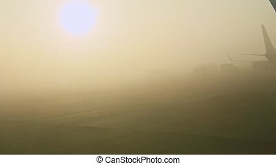 view from airplane window on two aircraft in fog on empty runway against sunrise