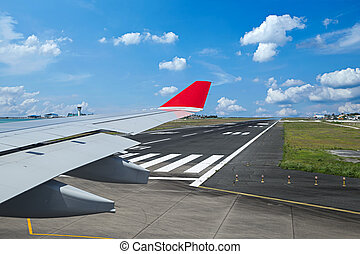 view from airplane with wing on airport runway ready for takeoff in front blue cloudy sky