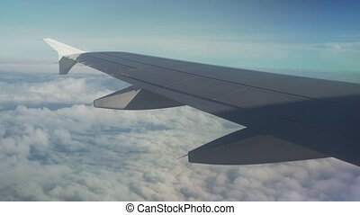 View from an airplane on wing of an airplane and cumulus...