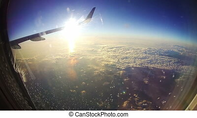 View from an Airplane Window above the Clouds on Sun Background