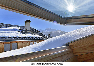 view from an opening window on a roof covering with snow in an alpine cottage