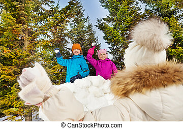 View from back of girl holding snowball to throw