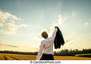 View from behind of a businessman standing in sawn field under evening sky