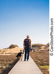 View from behind of a man walking with his dog on a road leading through beautiful landscape