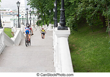 View from behind of cyclists descending steps