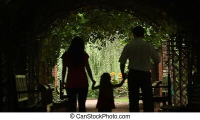 View from behind on parents with child walks in plant tunnel