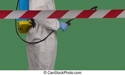 View from behind the signal tape a medical worker in a protective suit against bioviral hazard spray of chemicals for disinfection against coronavirus. Isolated on a green screen chroma key. Disinfection of the quarantine zone. Slow motion. Close up.