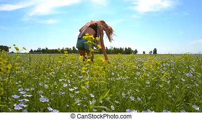 view from below girl in shorts touches buckwheat flowers