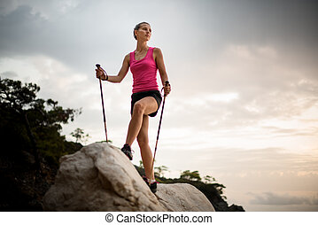 View from below of young athletic woman with trekking poles standing on large rock against background of sky and trees