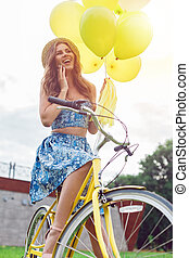 View from below portrait of a beautiful woman smiling on a bicycle on a summer day