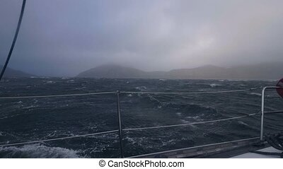 View from board yacht sailing on stormy sea waves. Sail boat...
