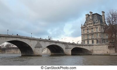 view from boat moving on Seine river near by bridge Pont Royal and Louvre, Paris