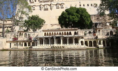 view from boat on lake and palaces in Udaipur India
